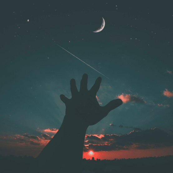 photo of a hand reaching for the new moon