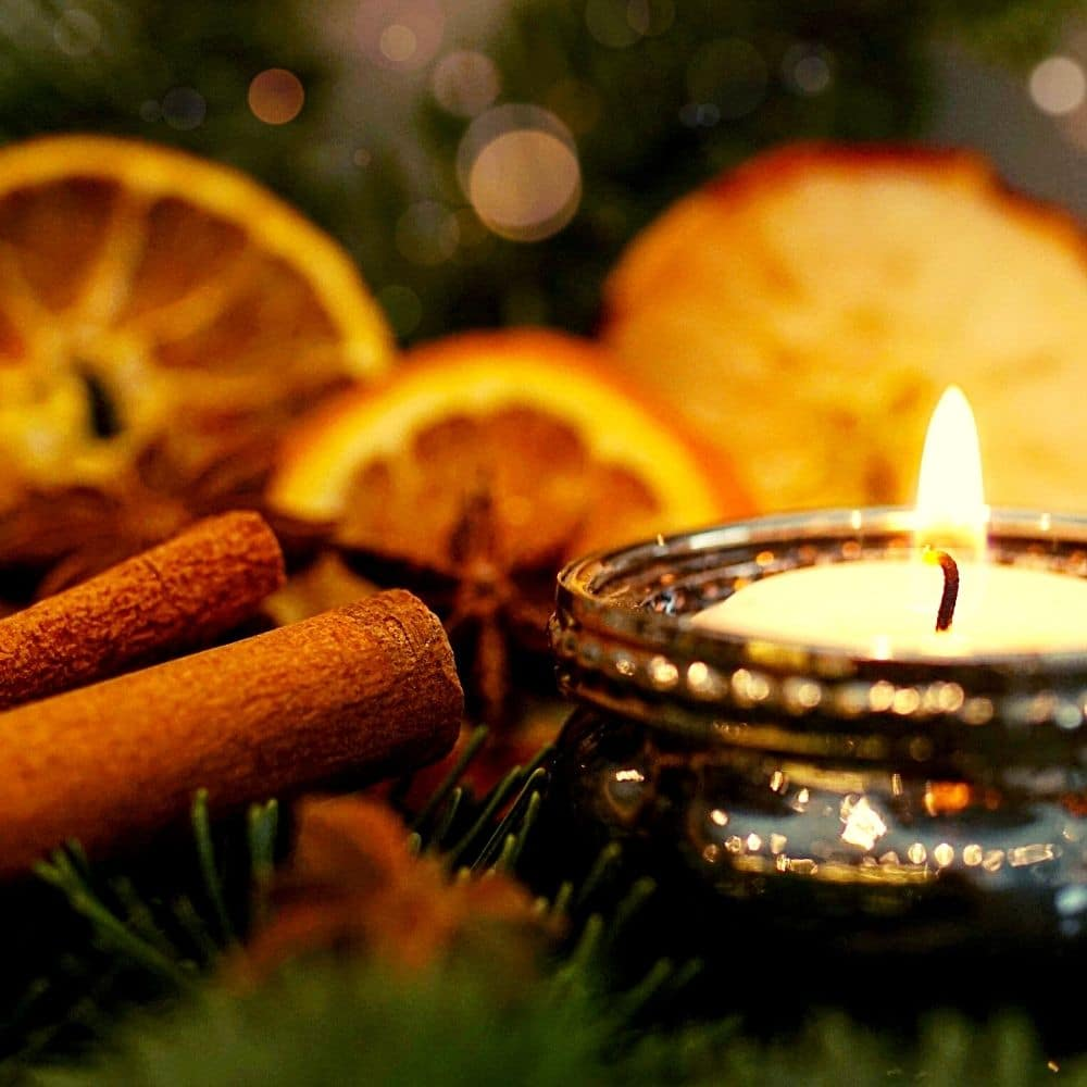 photo of yule altar decoration: candle, cinnamon and oranges