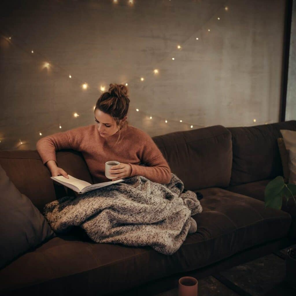 photo of a woman reading a book in a cozy living room