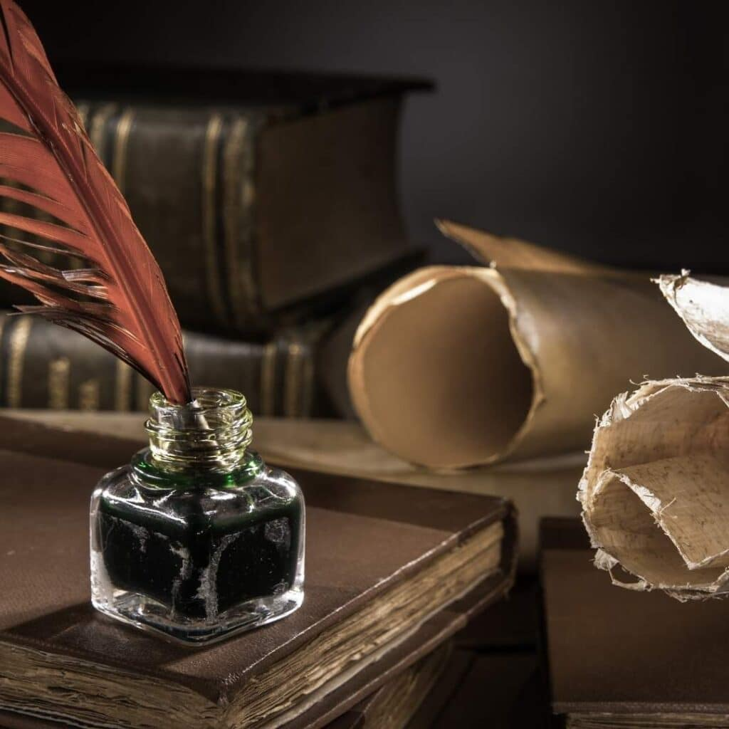 photo of a quill, ink and old paper