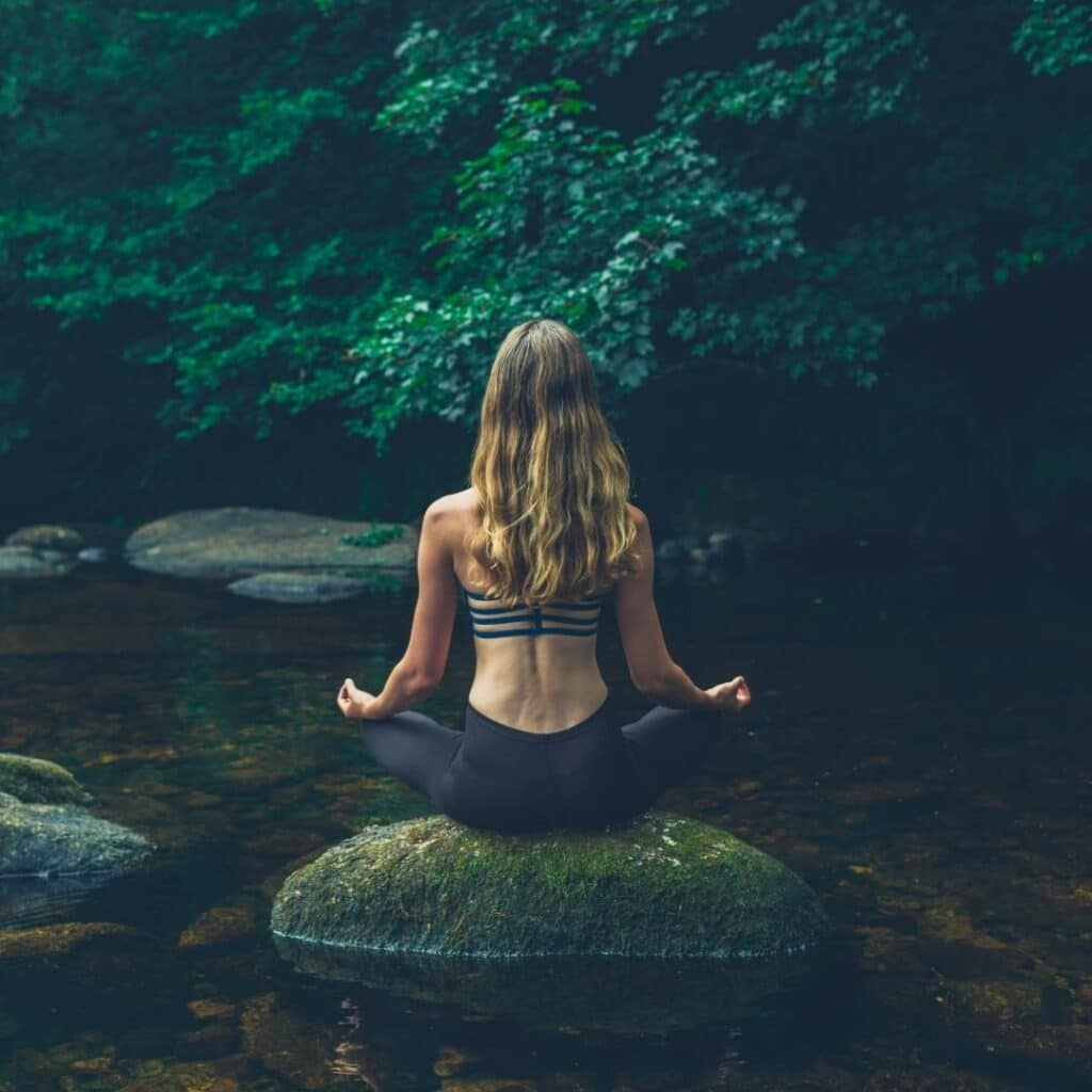 photo of a girl meditating on a rock